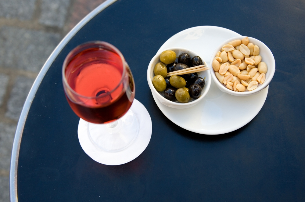 Parisian street cafe table with traditional French aperitif kir
