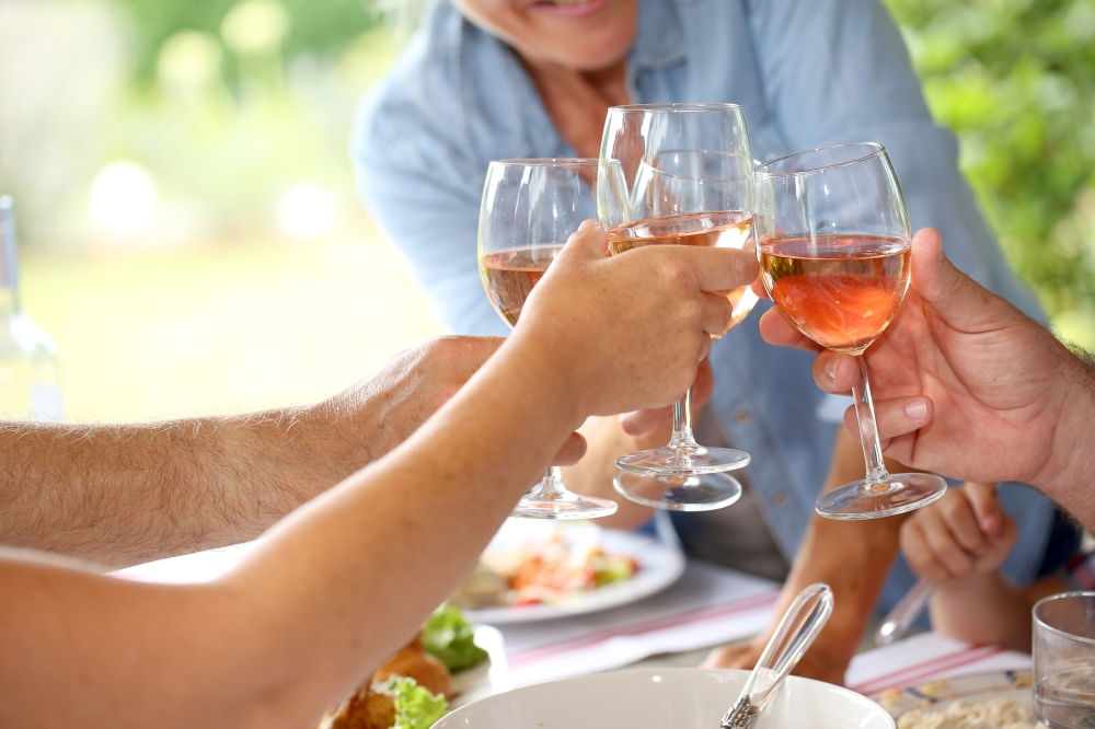 Closeup of wine glasses held by family at lunch